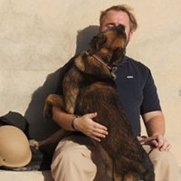 A K9 handler shares an affectionate moment with his dog